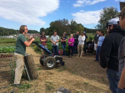 Student Farm intern Michael Cahill talks with a group of students about how to operate the tiller that he worked with all summer long.